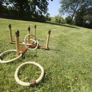 Quoits game is rope quoits and wooden pins with a wooden cross base